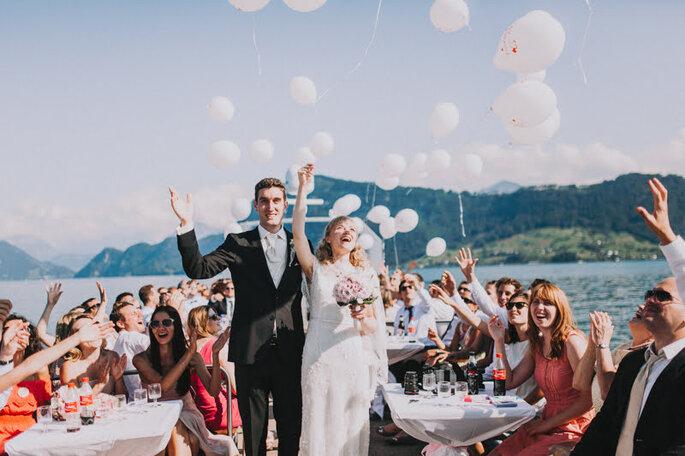 Die Hochzeitsgesellschaft von Elena & Ralf bei der Feierlichkeit am See vor dem Schloss Meggenhorn unter freiem Himmel.