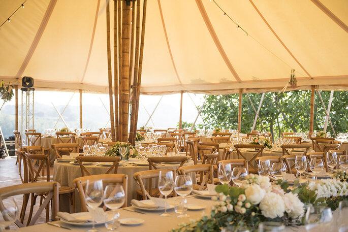 Dîner de réception installé sous une grande tente en extérieur.