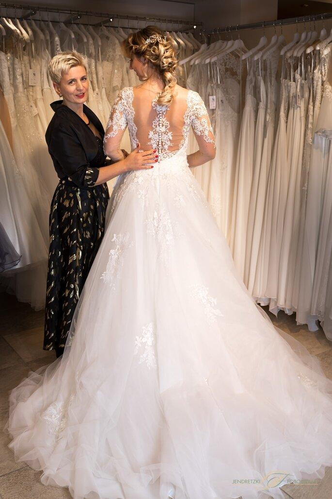 Haus der Braut-Geschäftsführerin Sabine Kuch in ihrem Geschäft mit einer Braut, die ein rückenfreies Brautkleid trägt.