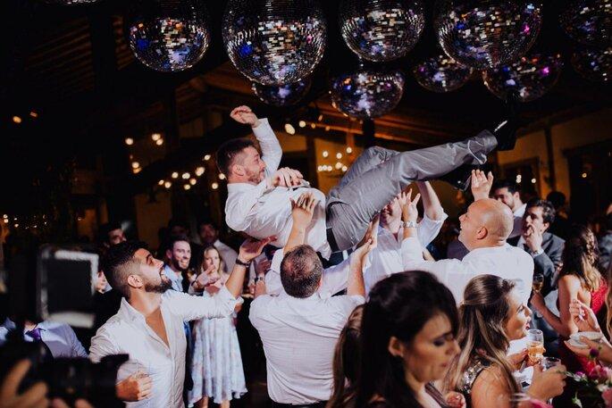 convidados carregam noivo em festa de casamento