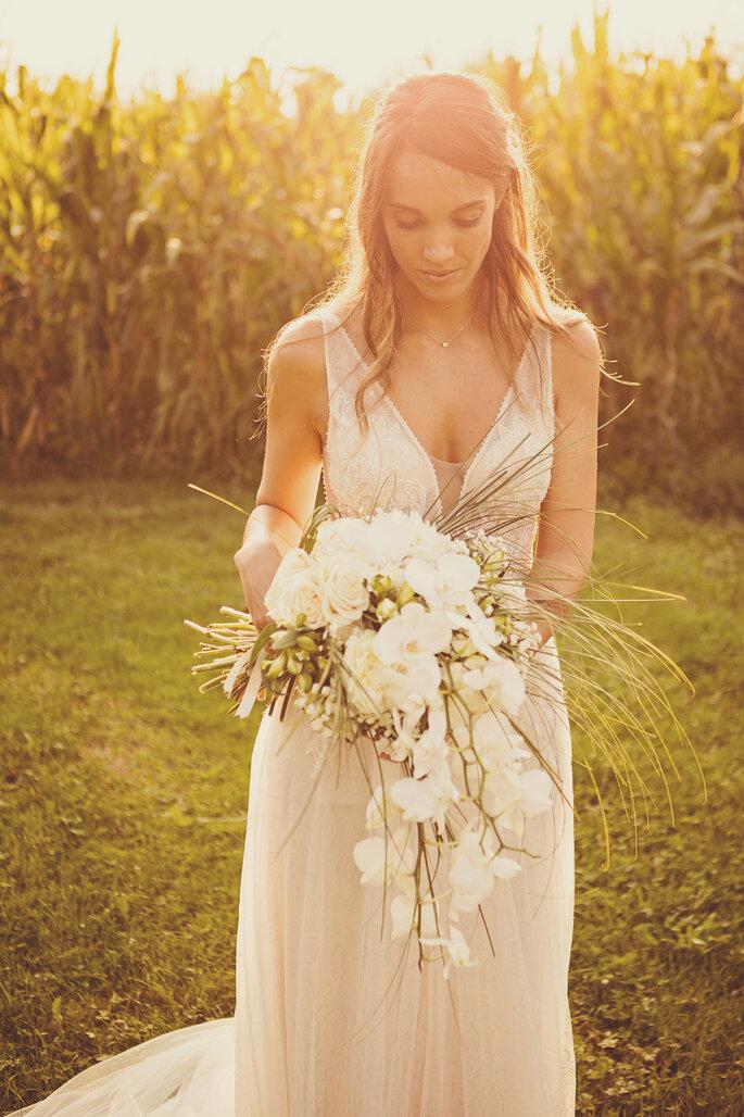 Hochzeitsfoto. Braut mit Brautstrauss vor Feld