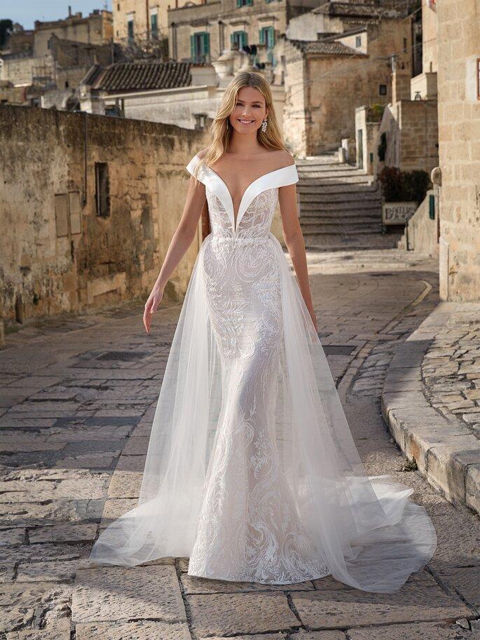 Vestido de novia con corte de sirena con pedrería, con mangas a los hombros, escote en V profundo y sobrefalda de tul