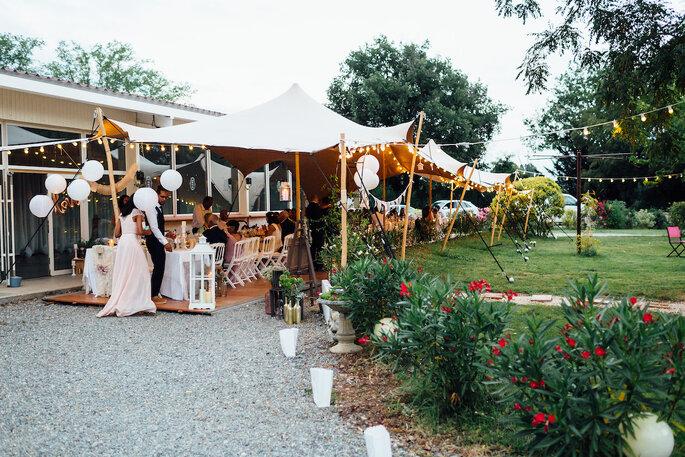 Tente installée en extérieur pour un dîner de réception.