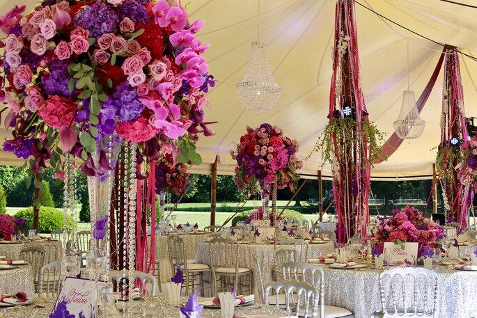 Compositions de fleurs, rubans et perles dans des tons roses, rouges et violets qui ornent une tente d'extérieur