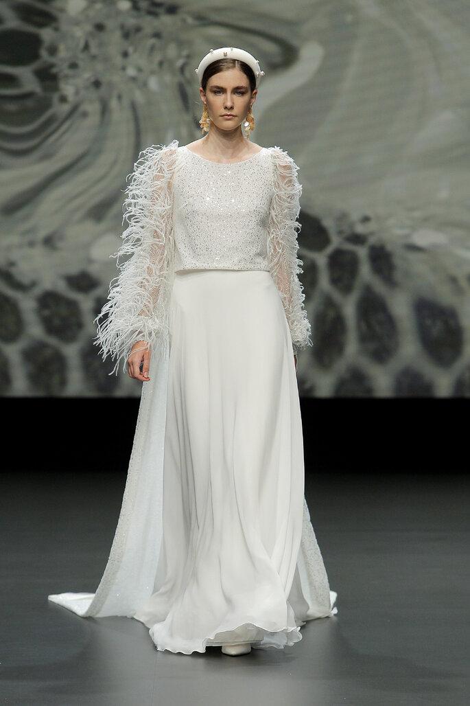 Colección Vestido de Novias 2021 Jesús Peiró vestido de novias alternativo de mangas largas decoradas por plumas, escote de cuello redondo y falda plisada