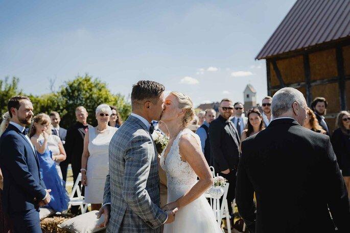 Hochzeitsfeier. Brautpaar küsst sich nach der Trauung. Im Hintergrund Hochzeitsgäste