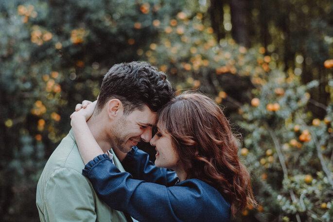 dois namorados agarrados com um bosque como fundo