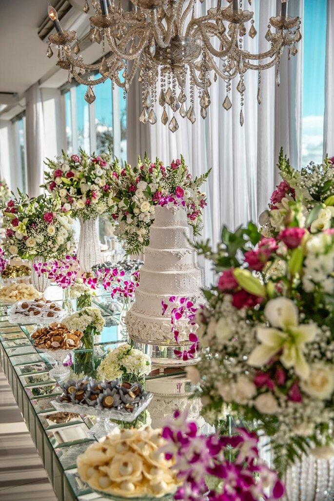 mesa decorada com flores, doces e bolo de casamento