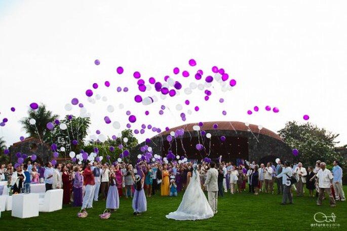 Los invitados y novios soltando globos morados en la recepción - Foto Arturo Ayala