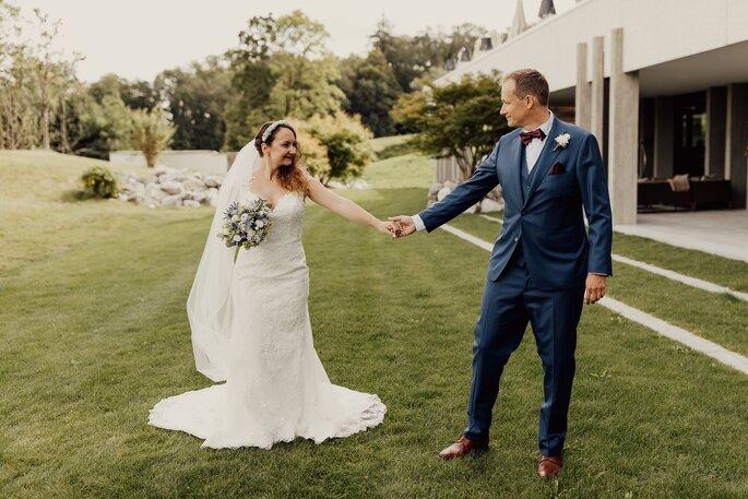 Brautpaar. Hochzeitsfoto des Brautpaares auf Wiese, händchen haltend