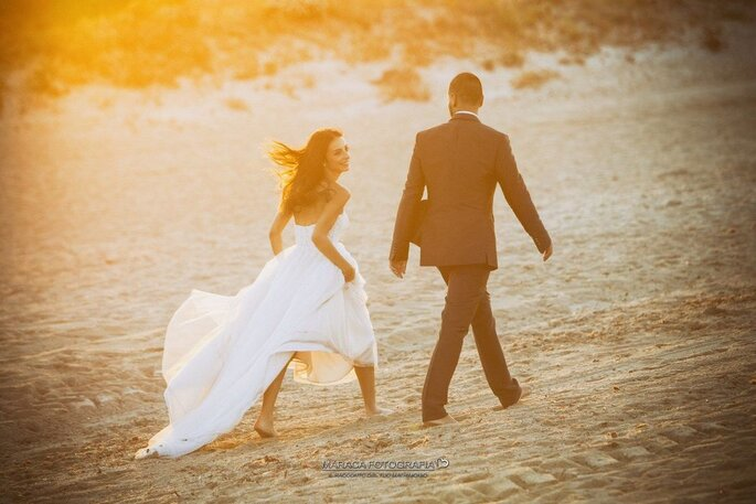 Coppia di sposi sulla spiaggia al tramonto
