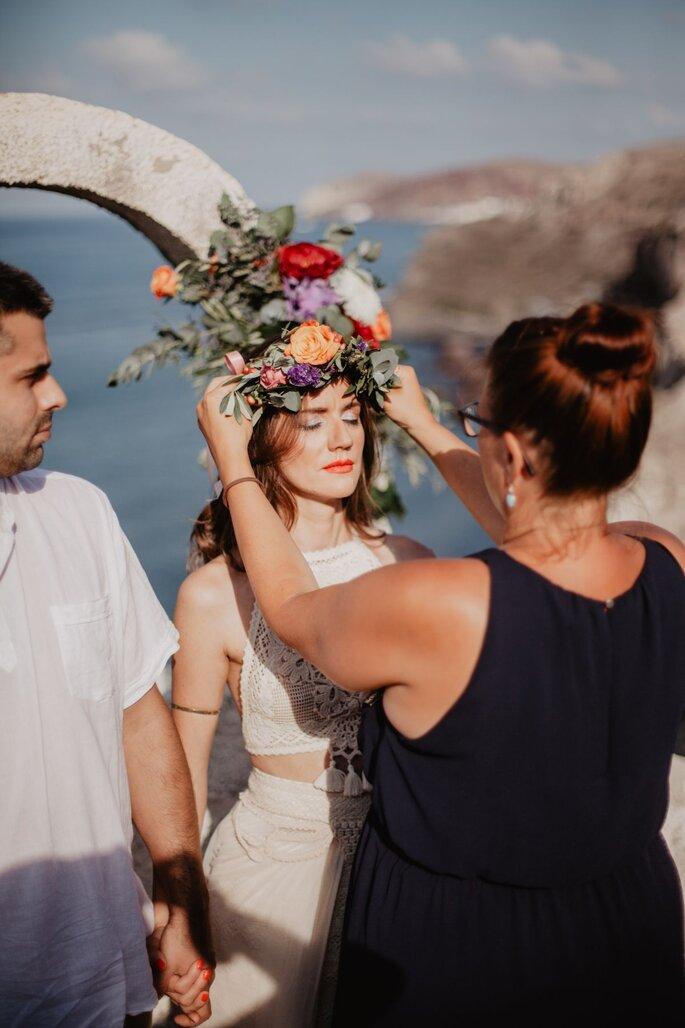 Eine Braut bekommt einen Blumenkranz aufgesetzt.