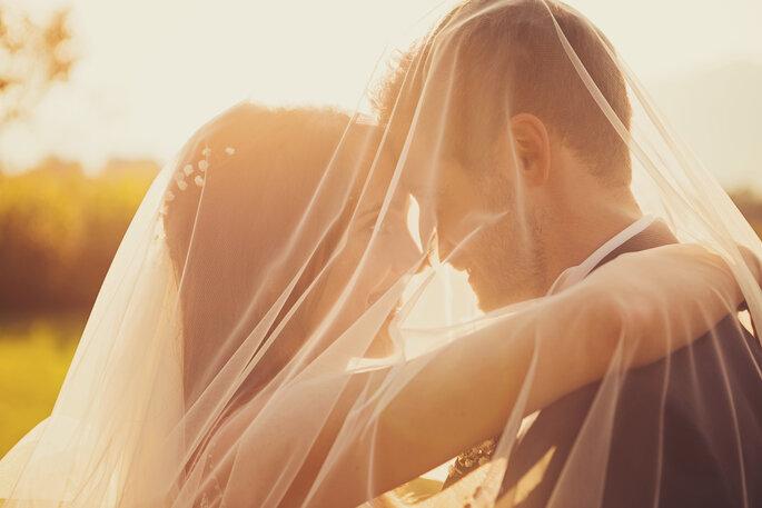 Hochzeitsfoto. Brautpaar schaut sich in die Augen vor Sonnenuntergang, verdeckt vom Schleier der Braut
