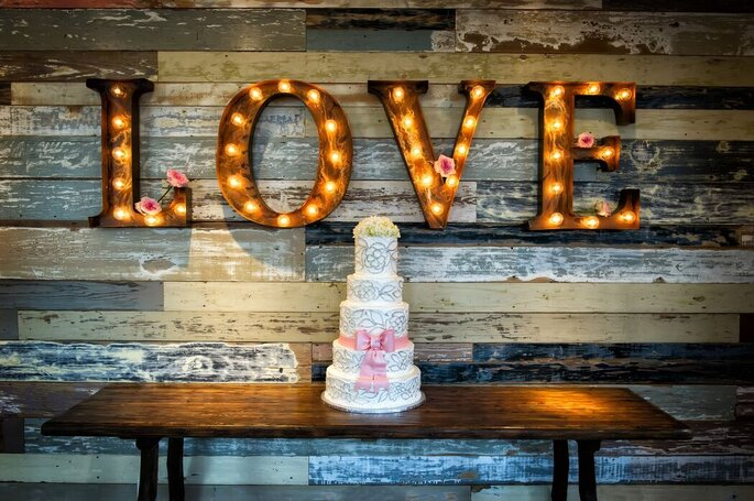 Une belle pièce montée de mariage et des lettres illuminées en guise de décoration