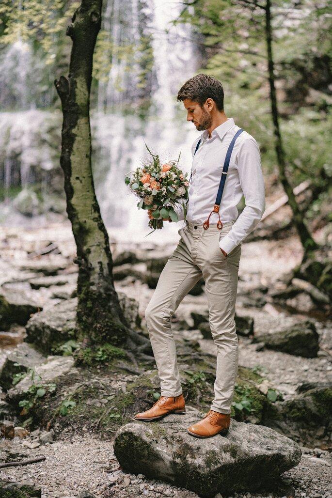Bräutigam zeigt sein Outfit vor dem Wasserfall und hält Strauß der Braut.