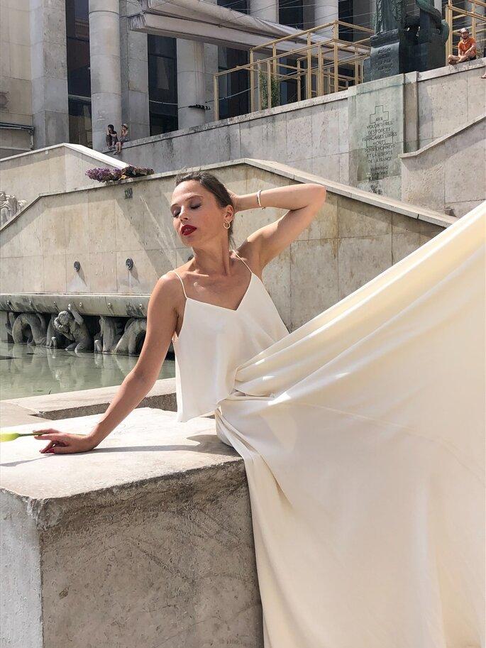 Robe de mariée deux pièces, blanche et fluide, portée par un mannequin assis tenant une fleur dans sa main et confectionnée par Oksana Coquard