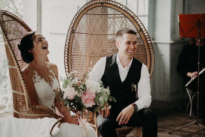 Ma petite cérémonie - Deux mariés en train de rire, assis sur des fauteuils en osier
