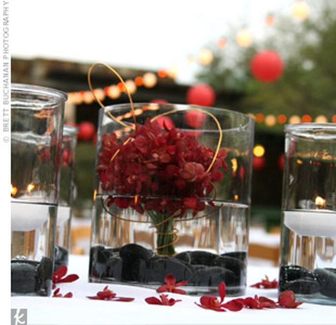Un centro de mesa con ramo y pétalos rojos dan un aire de distinción.