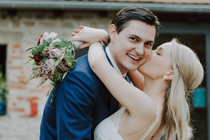 Braut küsst Bräutigam auf die Backe