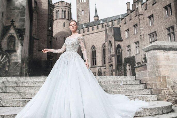 Vestido de novia con corte de princesa con mangas largas a los hombros y detalles de pedrería