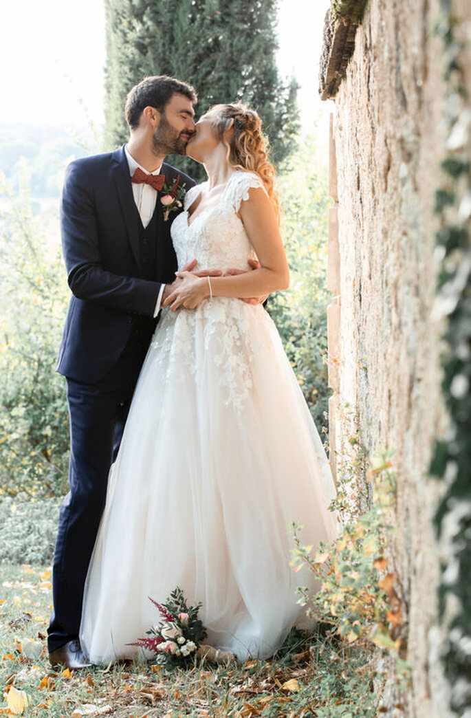 Un couple de mariée en train de s'embrasser et de s'enlacer dans un jardin