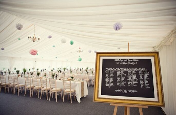 Eine Tafel, auf der die Tischnummern und die dazugehörigen Personen aufgelistet sind, ersetzt die Tischkärtchen – Foto: UKroserobin wedding