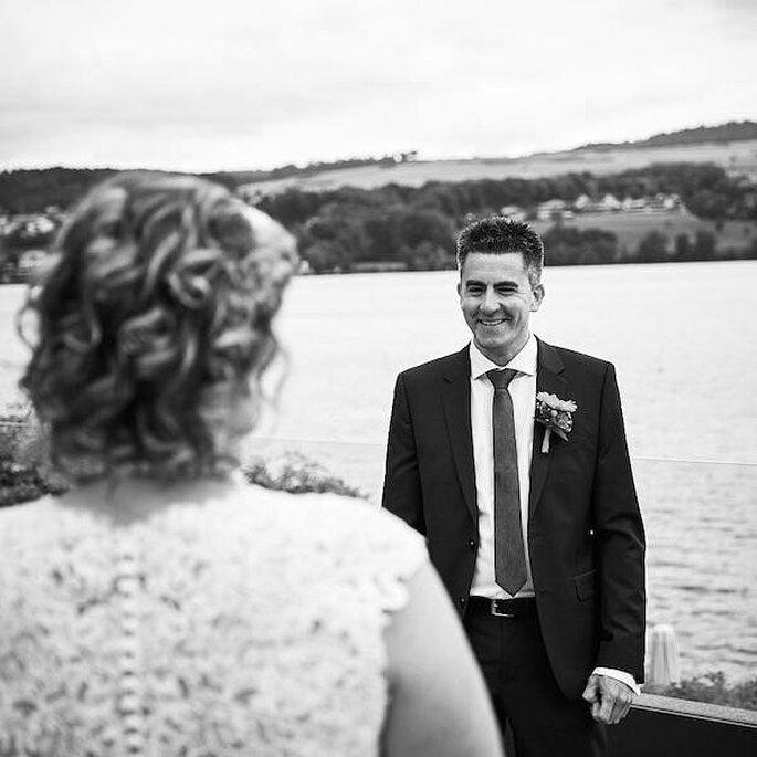 Eine Braut ist von hinten zu sehen, vor ihr steht ihr lächelnder Bräutigam.