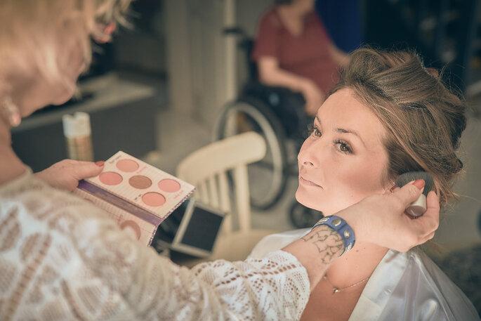 Une maquilleuse est en train de réaliser le make up d'une future mariée