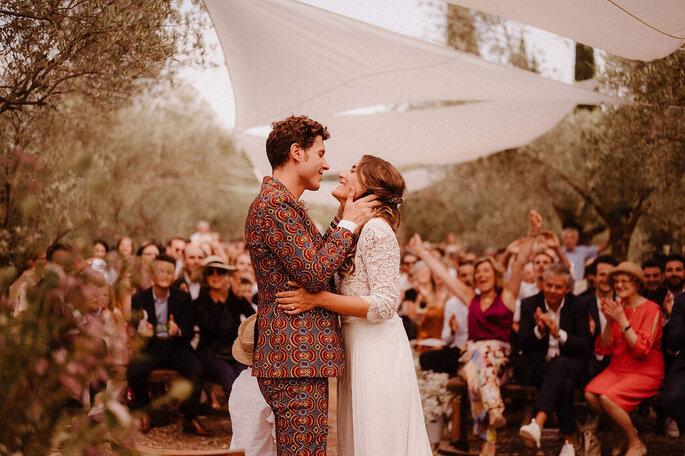 Un couple de mariés heureux lors de leur cérémonie laïque, le marié porte un costume coloré original