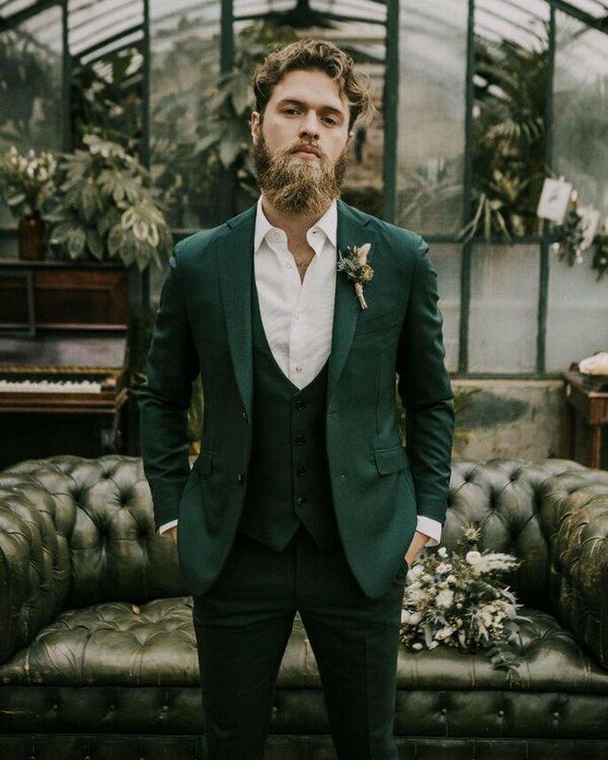 traje de novio en color verde sin corbata ni moño con chaleco verde y adorno floral