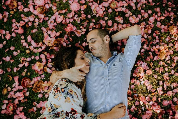 casal abraçado sobre cama de relva de pétalas de flores