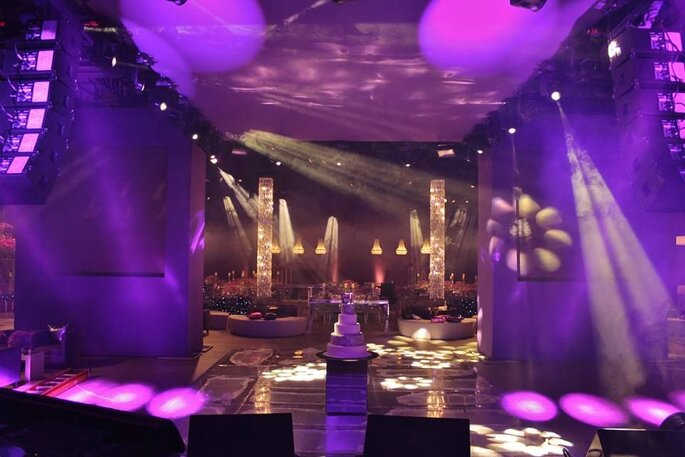luzes na pista de dança evidenciam bolo ao centro da festa de casamento