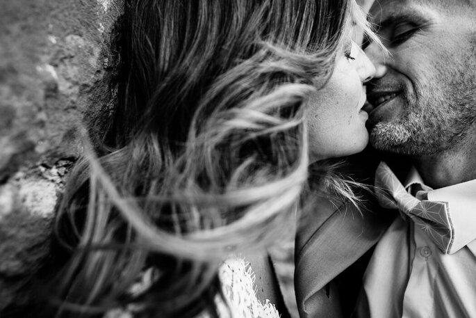 Photo en noir et blanc de deux mariés en train de s'embrasser