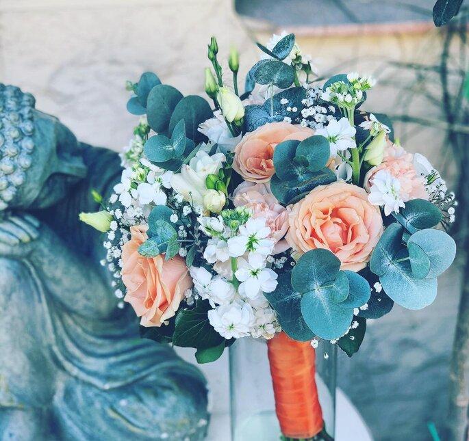 Bouquet de mariée rond sur mesure composé de végétaux, de roses oranges et de fleurs blanches