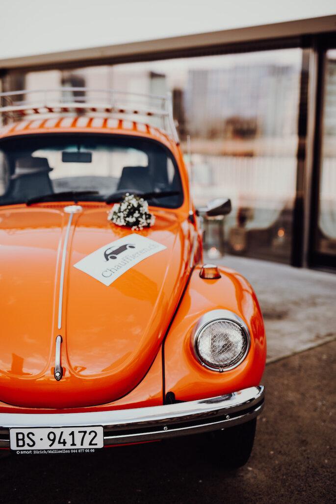Ein orangefarbener Oldtimer vor der Location der Hochzeitsmesse Bridal Teatime.