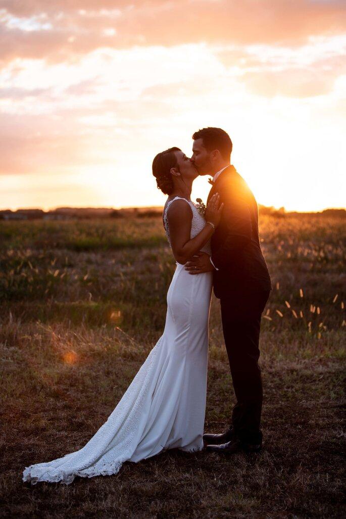 Photo d'un couple de mariés au coucher du soleil