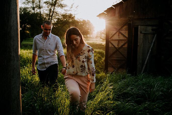 casal a andar de mão dada campo com casa de madeira romântico