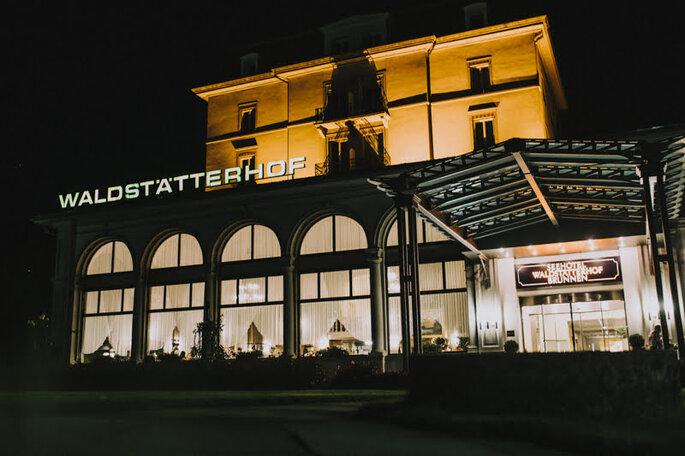 Blick auf das Seehotel Waldstätterhof bei Nacht – hier beginnt die Hochzeitsfeier von Elena & Ralf am Abend.