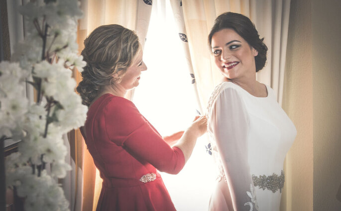 Hermana ayudando a vestirse a la novia