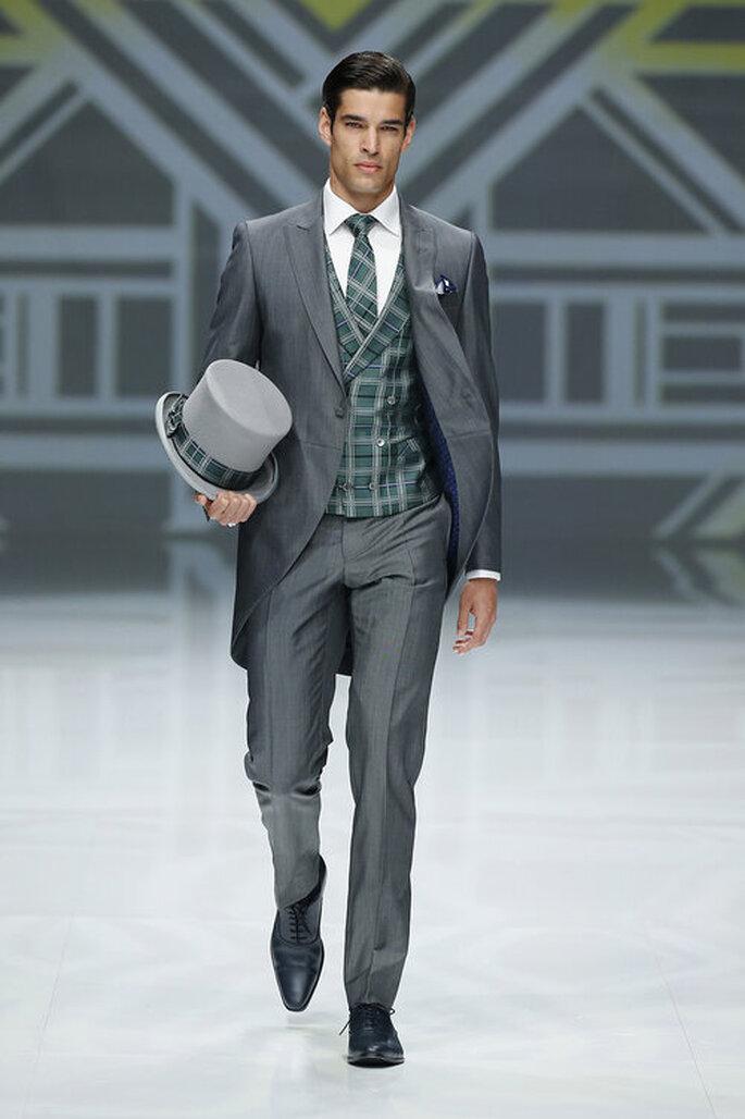 Traje de novio chaqué en gris con chaleco de cuadrados con corbata y accesorios como un sombrero