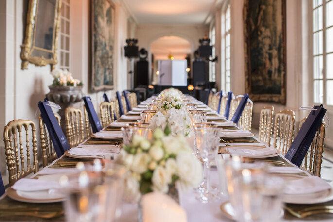 Alexandre Moulard - une table dressée pour un mariage chic, avec des bouquets de fleurs blanche et des chaises dorées