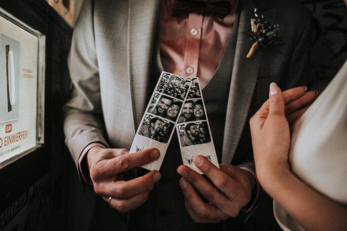 Der Bräutigam hält die Fotos as der Fotobox in der Hand, organisiert von Freakin' Fine Weddings.