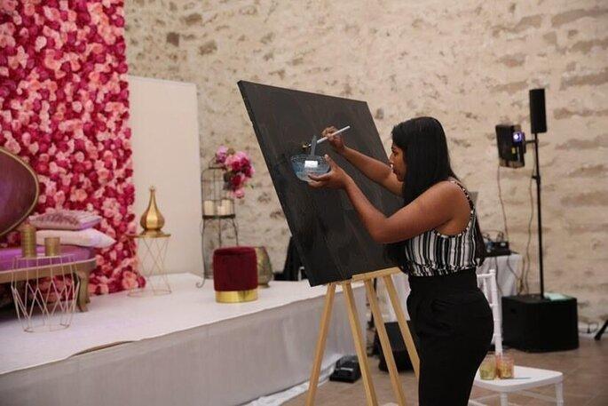 L'artiste Sharuki en train de peindre un portrait sur une toile pendant un mariage