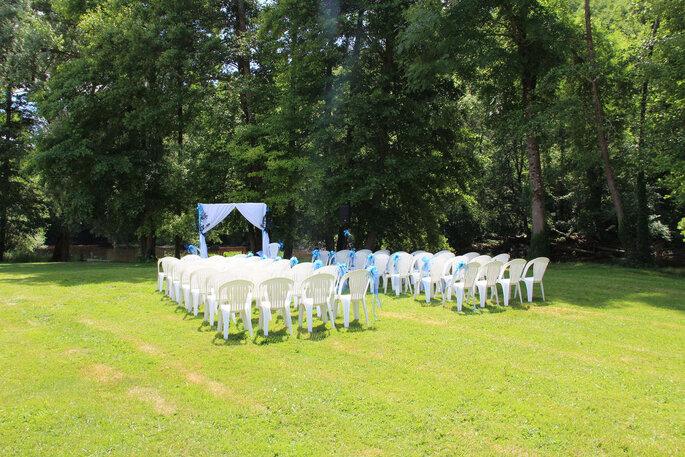 Une cérémonie laïque a lieu dans un parc arboré - des chaises et une arche blanche sont disposées en plein air pour les invités