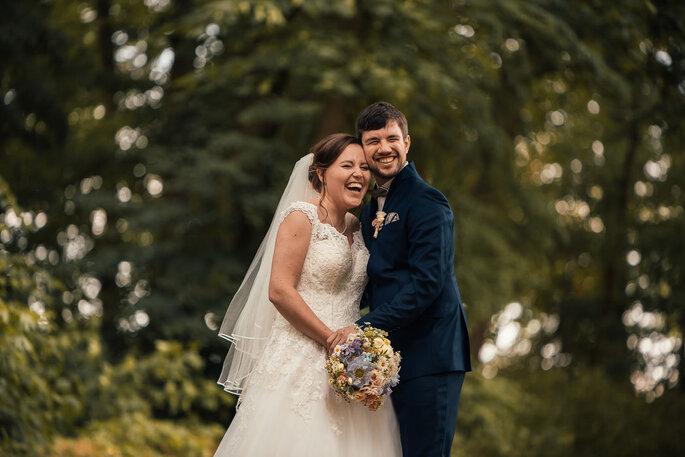 Ein Brautpaar steht mitten im Wald und lacht in die Kamera.