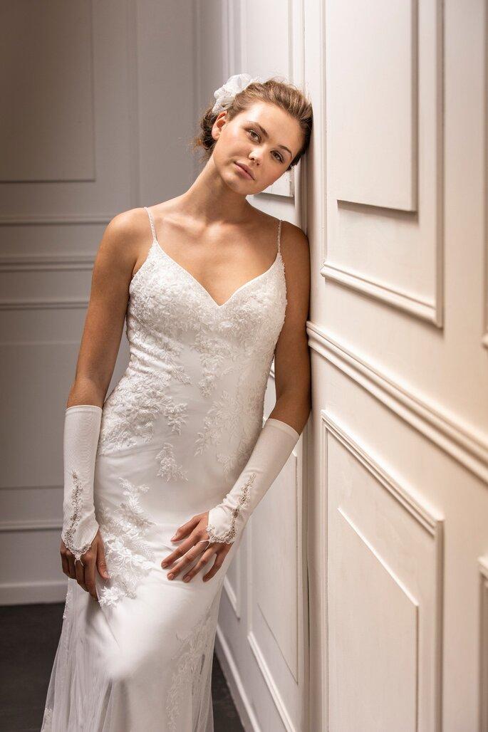 Les Mariées de Talia - Une mariée portant une robe à fine bretelle avec des feuilles en dentelles cousues tout en transparence et des gants