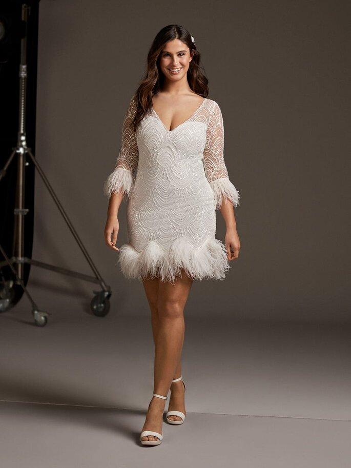 vestidos para gorditas Sensual vestido corto de tul bordado con pedrería, detalles de plumas en los perfiles de las mangas tres cuartos y en el acabado de la falda, y escote pico con transparencias.