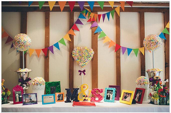 Mesa de dulces con las iniciales de los novios, banderines y portarretratos. Foto: We Heart Pictures