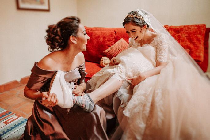 dama de honor probandole el tacón a la novia que se prepara para la boda