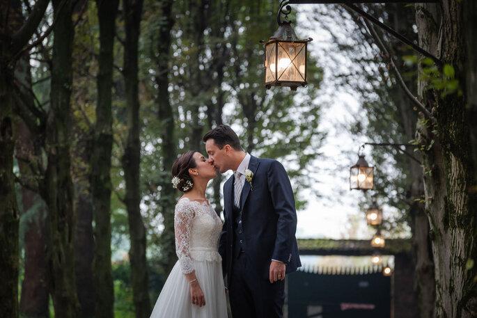Bacio coppia di neo sposi con lanterne romantiche